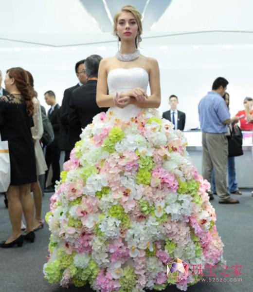 模特身着纯手工打造花朵礼服,佩戴品牌印记形象款