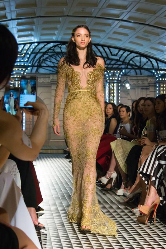 现场的光线射落在金黄色一字肩的直身裙上,令浅黄水晶机切平底石VIVA12®独有的12切面光芒更为璀璨,将Golden Era的面貌现于观众眼前