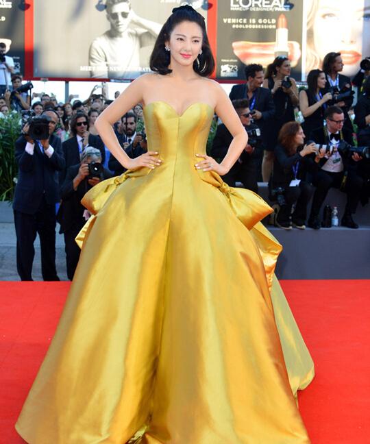 威尼斯开幕红毯:巨型钻石耳钉配金黄色缎面礼服